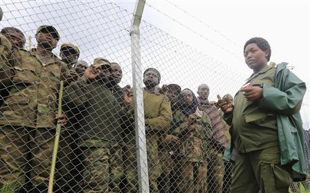 An army officer stands guards outside an enclosure filled with M23 rebel fighters who have surrendered to Uganda's government at Rugwerero village in Kisoro district